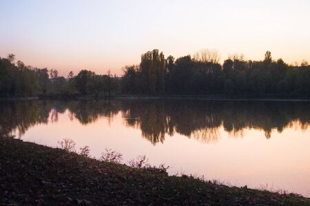 Autumn sunset in the park over the lake