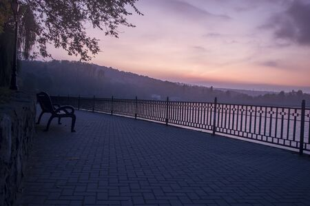 Park bench by the lake at sunset day
