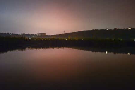 Late sunset over a lake in a park with red reflection