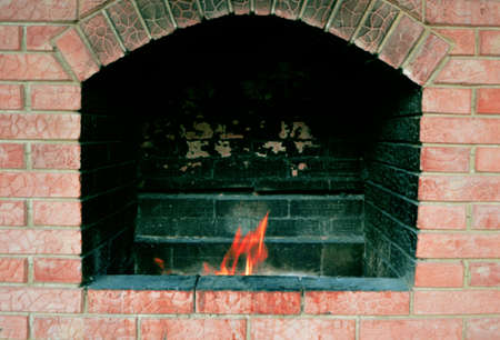 Fire place for cooking meat is made of brick with fire.