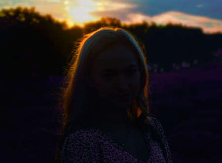 Romantic summer sunset with lighted hair of a girl in the center.