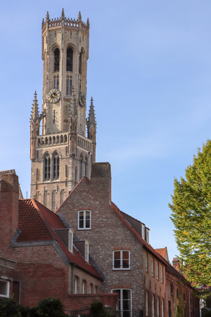 Traditional old church and houses typical of the skyline in Bruges Stock Photo