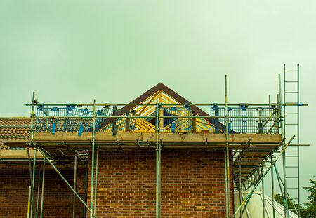 Scaffolding and wooden planks erected around an extension to a house Stockfoto