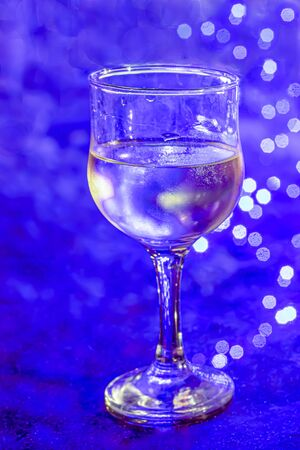 A glass of chilled white wine against a blue background Stockfoto