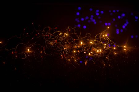 A string of shining fairy lights against a dark background