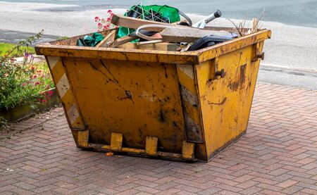 A yellow skip full of rubbish ready to be collection