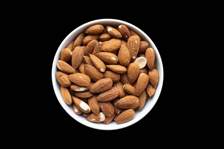Pot of ready to eat almonds isolated on a black background