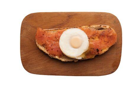 Saumon fumé et oeuf poché sur toast sur une planche en bois isolé sur fond blanc