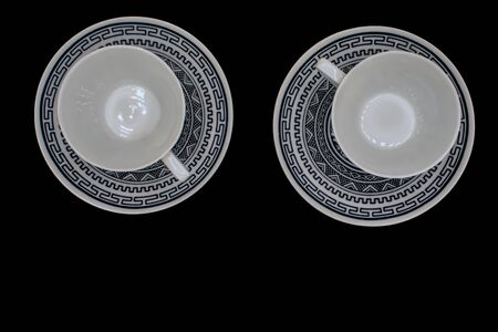 Top-down view of two coffee cups and saucers isolated on a black background Reklamní fotografie