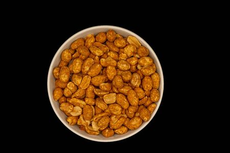 A white dish of dried roasted peanuts isolated on a black background