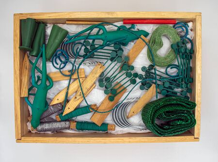 overhead view of a wooden box of gardening accessories isolated on a light background 免版税图像