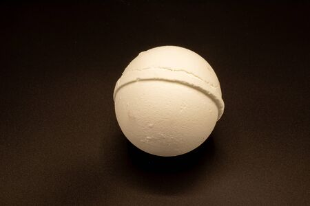 Top down view of a bath bomb isolated on a dark background