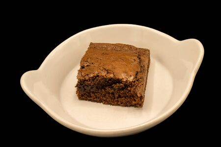 Top down view of a piece of home-made chocolate brownie isolated on a black background