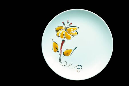 A white plate decorated with flowers made from food coloring isolated on a black background