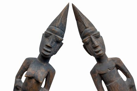 Front view of two Nigerian carved figures isolated on a white background