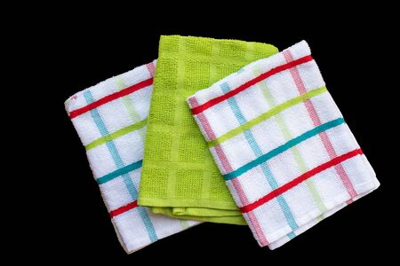 Top down view of three tea towels isolated on a black background