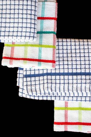 Top down view of four tea towels isolated on a black background