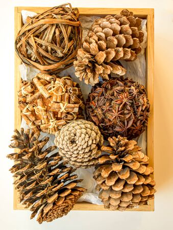 Seven pine cones in a wooden box isolated on a white background