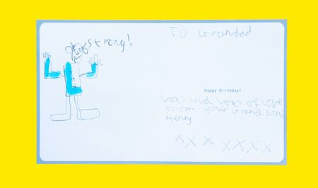 A seven year old boy writes and draws on a birthday card for his grandfather