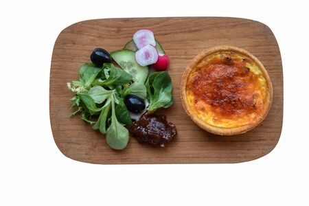 Quiche salad and chutney accompaniment on a wooden board isolated on a white background 免版税图像