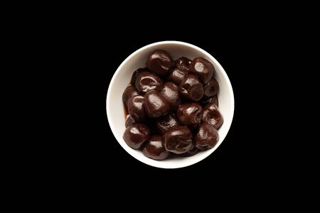 top down view of preserved cherries in a dish isolated on a black background