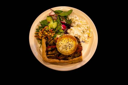top down view of home made- goat cheese tart and salad isolated on a black background 免版税图像