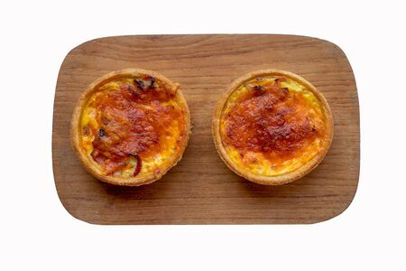 Two Quiche Lorraine tarts on a wooden board isolated on a white background