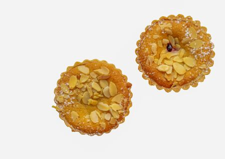 Top-down view of two cherry bakewell tarts isolated on a white background