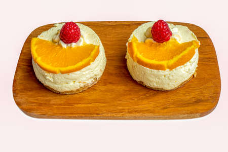 A plate of two raspberry and orange cheesecakes isolated on a white background 免版税图像