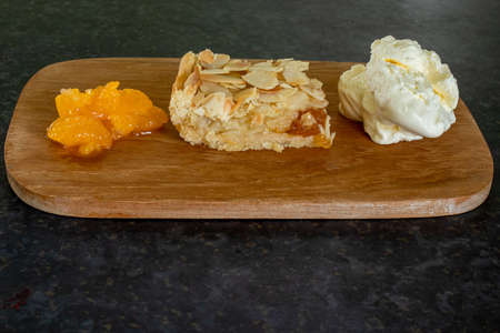 A portion of almond slice consisting of rose pastry, frangipane filling and almond flakes