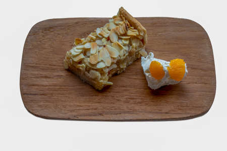 A portion of almond slice with whipped cream, orange and consisting of rose pastry, frangipane filling and almond flakes 免版税图像