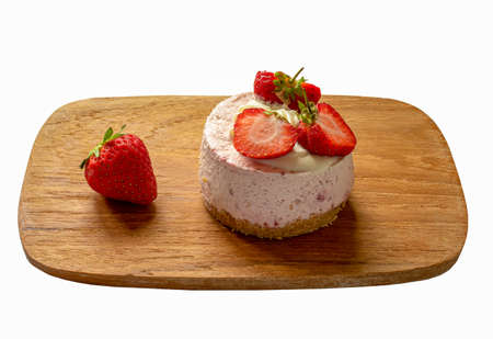 A piece of strawberry cheese cakes on a wooden plate isolated on a white background 免版税图像
