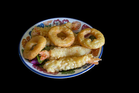 top-down view of a plate of tempura prawns and calamari rings isolated on a black background