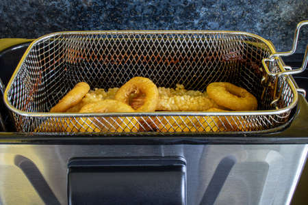 A side view of a deep fat frier used to cook rings of squid