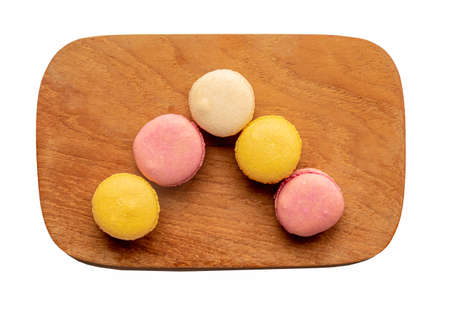 Top down view of a wooden plate of macaroons isolated on a white background 免版税图像