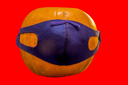 A side view of a pumpkin for halloween covered in a face mask for protection during the pandemic