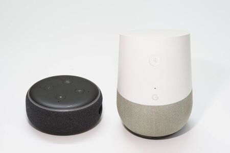 Amazon Echo dot and Google Home side by side on a white background