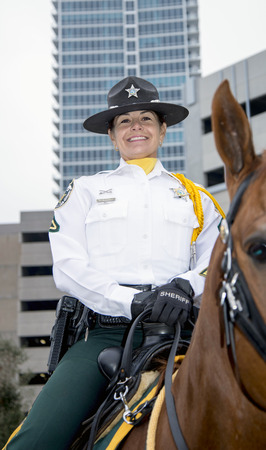 florida citrus: ORLANDO FL - December 30, 2013 -  Portrait of Female policeman in horseback at Florida Citrus Parade in Orlando Florida