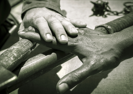 rudimentary: Hand of a caucasian man over a hand of an african man and rudimentary weapons, Italy.