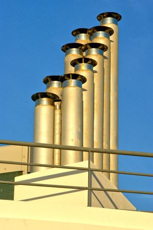 Multiple chimneys under blue sky Banco de Imagens