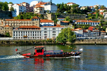 Tourist boat on Douro river overlooking Porto, Portugal