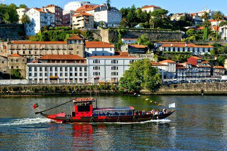 Tourist boat on Douro river overlooking Porto, Portugal