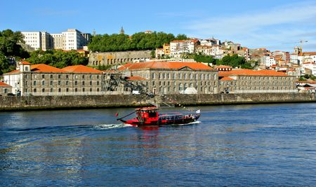Tourist boat on Douro river overlooking Porto, Portugal Banco de Imagens - 132892345