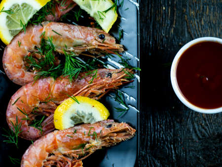 Boiled shrimps with lemons, greens and sauce on a wooden background. Top view
