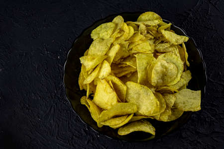 Potato chips on a stone background