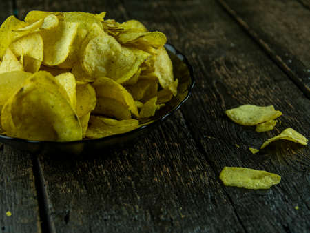 Potato chips on wooden background