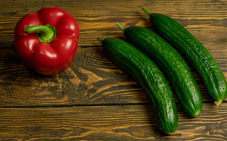 Fresh green cucumbers and sweet pepper isolated on wooden background