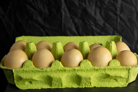 paper box with farm fresh chicken eggs on black background