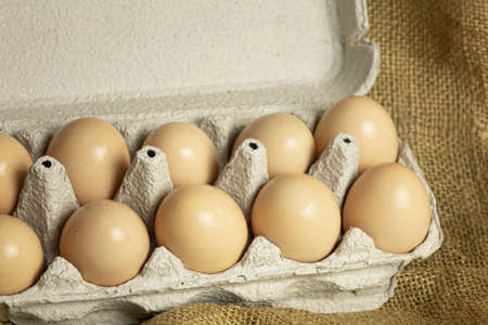 paper box with farm fresh chicken eggs on sackcloth background Imagens