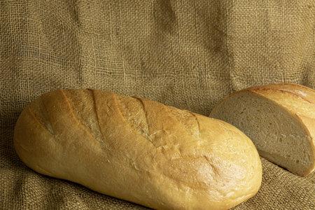 Fresh handmade bread on sackcloth background